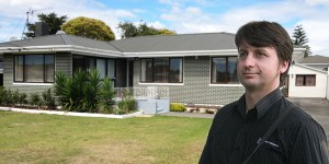 Rene McLean beside a typical Manurewa home that he regularly values.